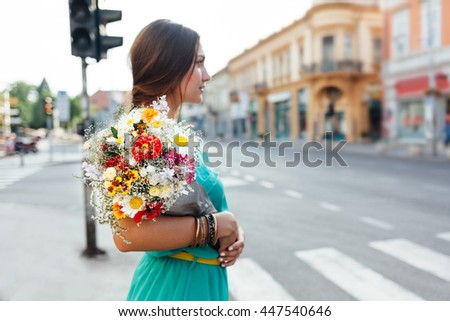 Beautiful woman with bouquet of flowers waiting in front of pedestrian crossing - stock photo