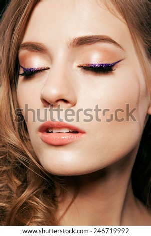Beautiful woman with bright make up eye with sexy purple sparky gloss liner makeup. Fashion big arrow shape on woman's eyelid. Chic evening make-up, healthy face - stock photo