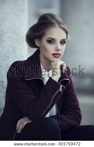 beautiful woman with bright makeup wearing a warm jacket in the street - stock photo