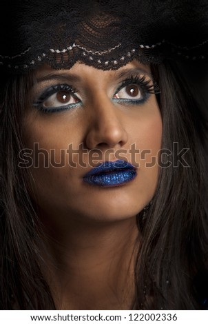 Beautiful woman with brown eyes, blue makeup and lips, and head covered in black lace staring upwards