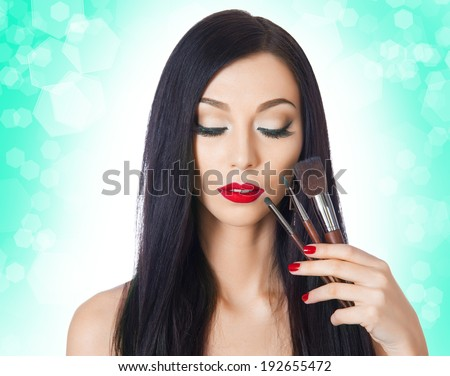 beautiful woman with brushes for makeup on the background bokeh