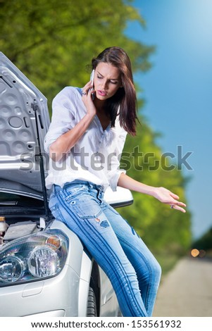 Beautiful woman with car trouble talking over a phone - stock photo