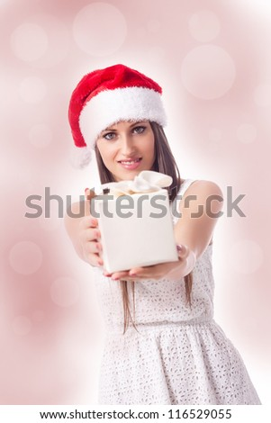 beautiful woman with christmas hat is giving a gift