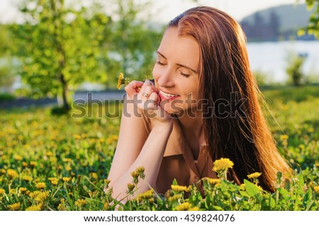 beautiful woman with closed eyes dreaming of lying on a meadow with dandelions in summer Park at sunset