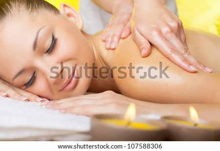 Beautiful woman with closed eyes getting a massage in the spa salon - stock photo