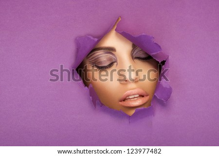 Beautiful woman with closed eyes looking through a torn hole in a sheet of purple paper with copyspace - stock photo