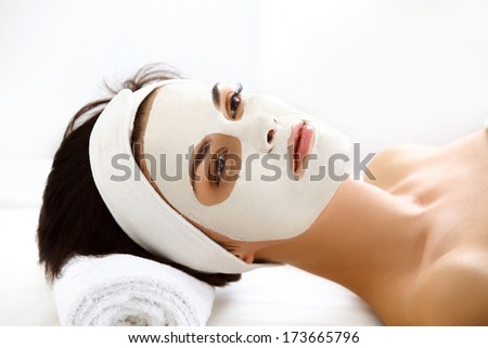 Beautiful Woman With Cosmetic Mask on Face. Girl Gets Treatment in Spa Salon against white Background - stock photo