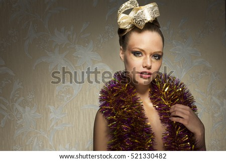 beautiful woman with creative golden make-up, ribbon in the hair style and sparkle tinsel on her shoulders.
