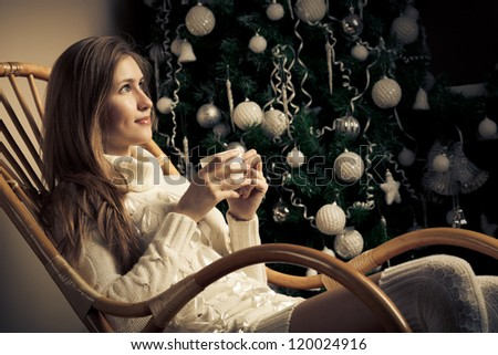 Beautiful woman with cup of coffee in chair. Christmas  decoration - stock photo