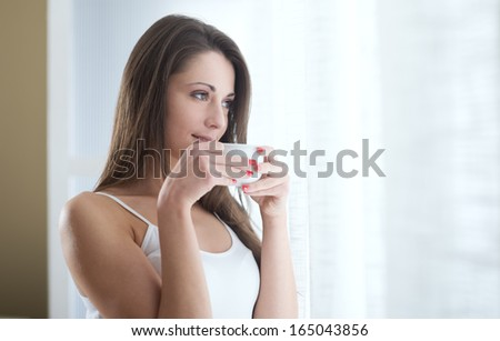 Beautiful woman with cup of coffee looking out of window.