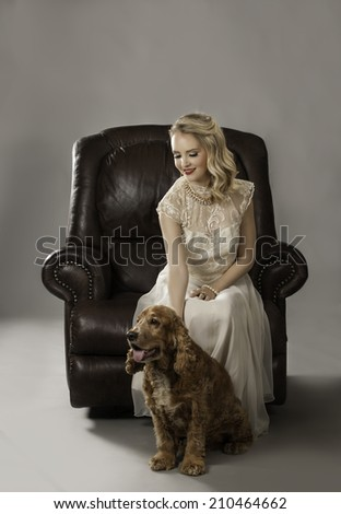 Beautiful woman with curly blonde hair and red lipstick wearing vintage evening dress of cream seated on brown leather couch with adorable Spaniel dog at her feet - stock photo