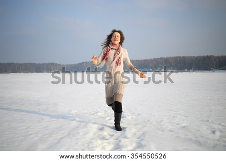 Beautiful woman with curly hair in a beige dress running in the snow - stock photo