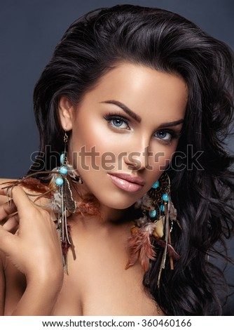 Beautiful woman with curly long hair posing on dark background - stock photo
