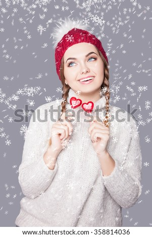 Beautiful woman with dark hair in  cap and a sweater under the snow,the joy on her face,prominent gorgeous smile,white teeth,girl looking to the top on a gray background in the studio.Woman and snow.  - stock photo