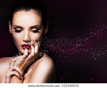 beautiful woman with dark makeup and purple lipstick posing on black background