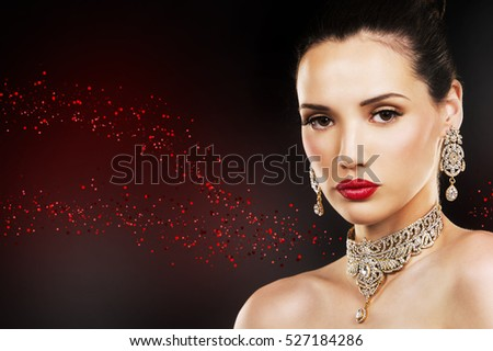 beautiful woman with dark makeup and red lipstick posing on black background