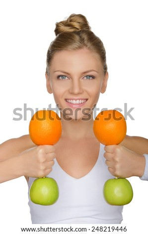 beautiful woman with dumbbells from apples and oranges isolated on white - stock photo