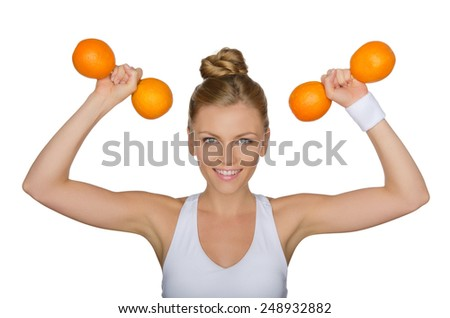 Beautiful woman with dumbbells from ripe oranges isolated on white - stock photo