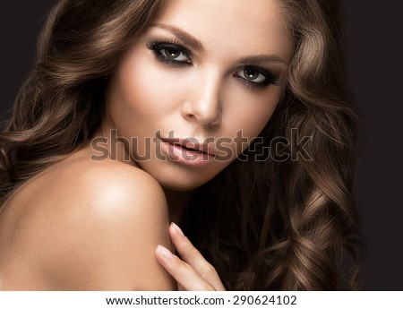 Beautiful woman with evening make-up and long straight hair . Smoky eyes. Fashion photo. Picture taken in the studio on a black background. - stock photo