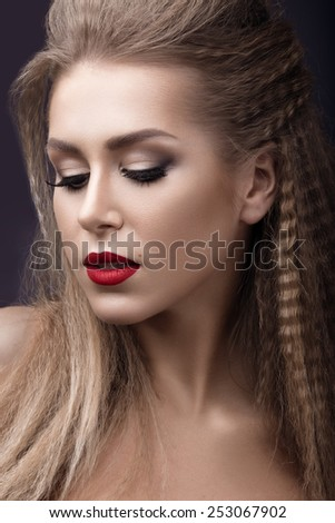 Beautiful woman with evening make-up, red lips and curls. Beauty face. Picture taken in the studio on a grey background.