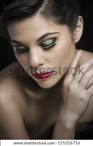 Beautiful woman with eye makeup and lash extensions - lips gloss and salon styled hair - stock photo