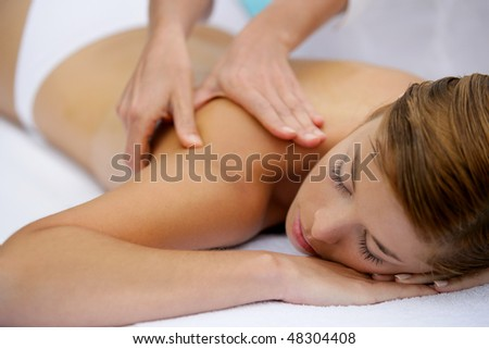 Beautiful woman with eyes closed having a body massage - stock photo