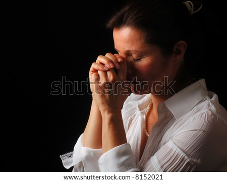 Beautiful woman with eyes closed in fervent prayer - stock photo