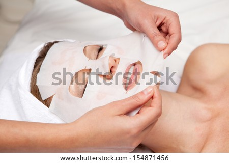 Beautiful woman with facial mask - stock photo