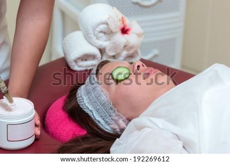 Beautiful woman with facial mask at beauty salon - stock photo
