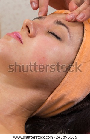 Beautiful woman with facial mask at beauty salon.Pretty woman receiving facial massage.Spa therapy for young woman receiving facial mask at beauty salon - indoors - stock photo