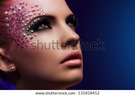 Beautiful woman with fantasy makeup on a blue background - stock photo
