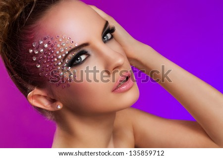 Beautiful woman with fantasy makeup on a violet background - stock photo
