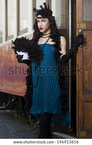 beautiful woman with feather dusters and fan stands in front of the tram, 1930s - stock photo