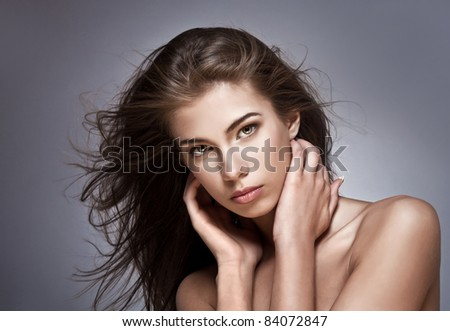 Beautiful woman with fluttering hair. On dark background. - stock photo