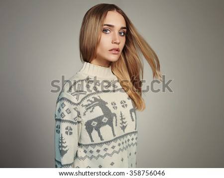 Beautiful Woman with flying hair in winter pullover. Beauty Blond Girl. Healthy hair - stock photo
