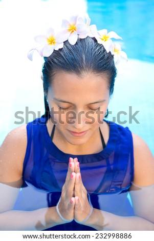 Beautiful woman with frangipani flowers in her hair, praying pose in swimming pool - stock photo