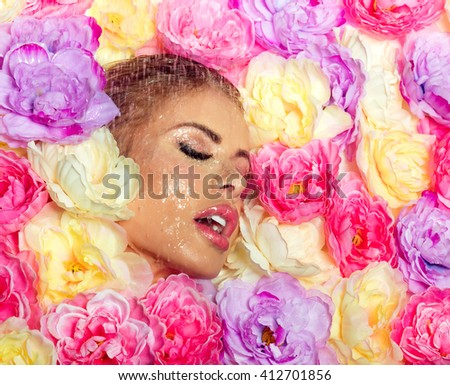 Beautiful woman with glamour makeup posing over colorful flowers. Closeup beauty portrait. Spring style. Shower. - stock photo