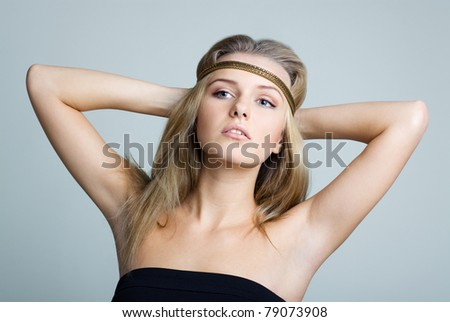 BEAUTIFUL WOMAN WITH GOLD JEWELRY BAND. Her hands behind head showing the armpits. - stock photo