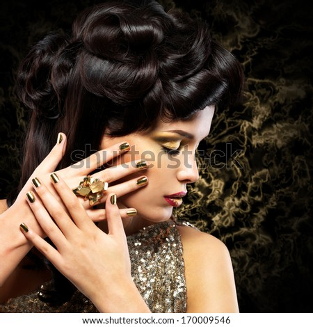 Beautiful  woman with golden nails and fashion hairstyle over creative background