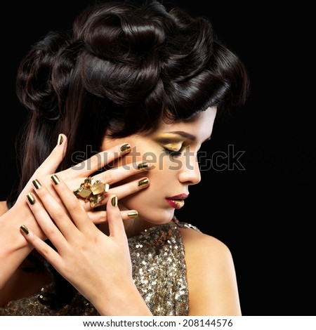 Beautiful  woman with golden nails and fashion makeup of eyes. Brunet girl model with style hairstyle on black background - stock photo