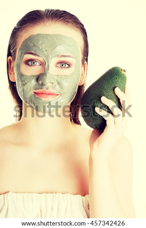 Beautiful woman with green avocado clay facial mask - stock photo