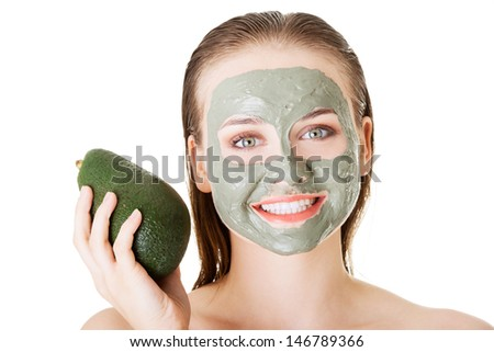 Beautiful woman with green avocado clay facial mask, isolated on white - stock photo