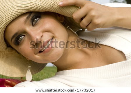 Beautiful woman with green eyes smiling holding her hat's brim - stock photo