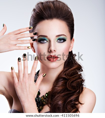 Beautiful woman with green make-up and creative color of nails - stock photo