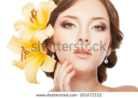 Beautiful woman with hairstyle, bright makeup, manicure. With lily flowers