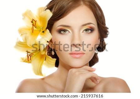 Beautiful woman with hairstyle, bright makeup, manicure. With lily flowers - stock photo