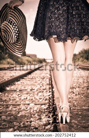 Beautiful woman with hat walking over railroad. Sepia style. - stock photo