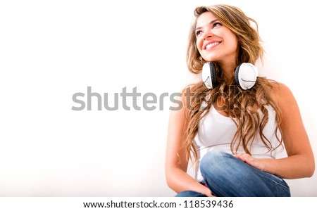 Beautiful woman with headphones daydreaming - isolated over white - stock photo