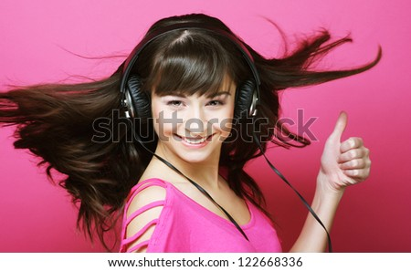 Beautiful woman with headphones, she is listen to the music over pink background - stock photo