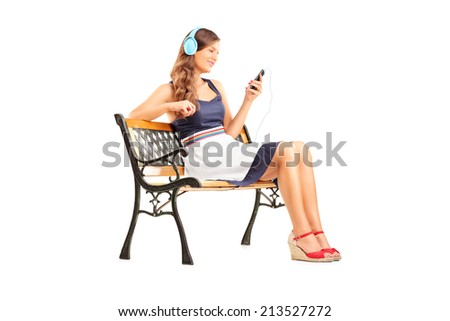 Beautiful woman with headphones sitting on bench isolated on white background - stock photo